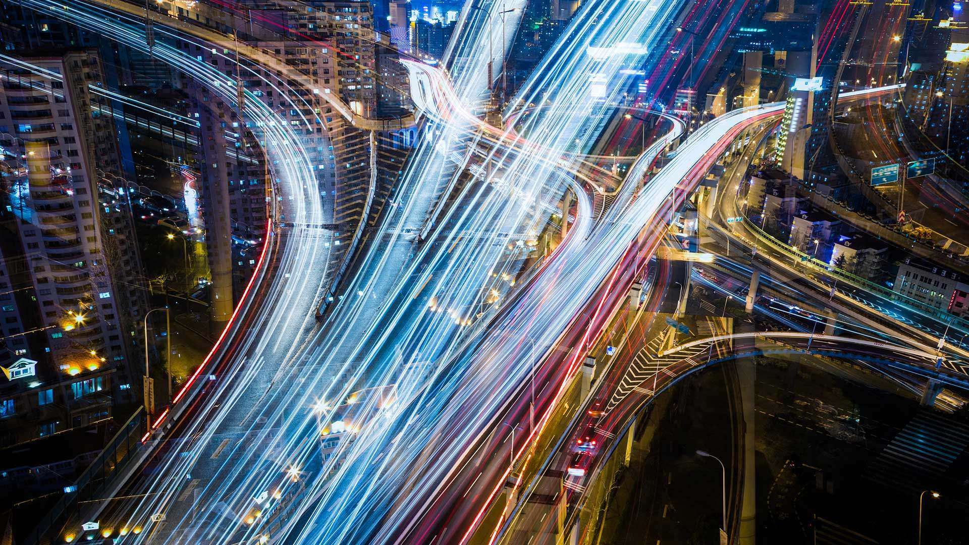 A long exposure photo of automotive traffic in a city at night