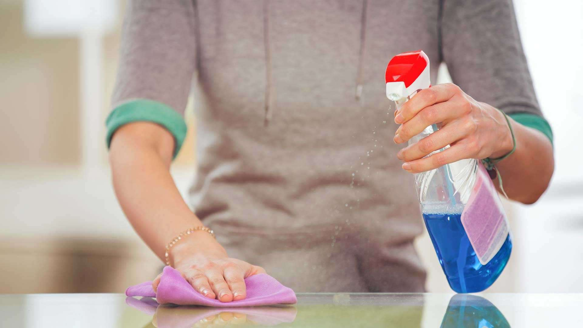 A photo of a person using a spray cleaning product.