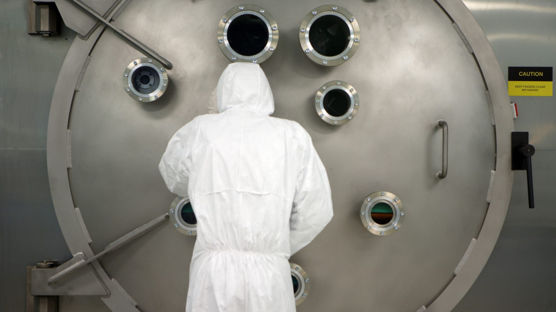 A photo of a CPI staff member using a large area atomic layer deposition equipment in a cleanroom