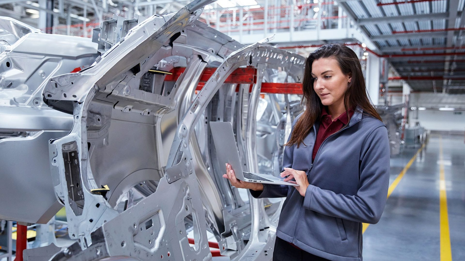 A photo of a lady inspecting a car manufacturing line