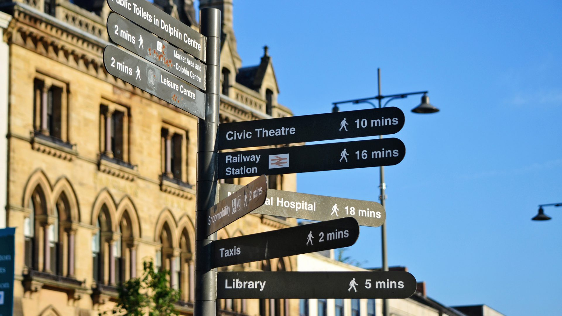 A photo of a wayfinding sign in Darlington pointing to the train station and taxi queue