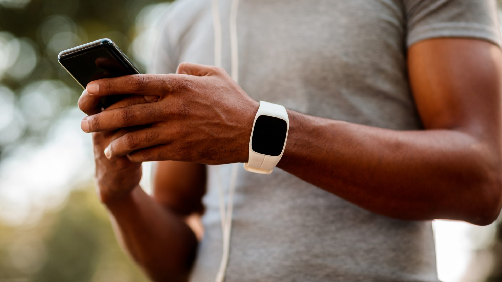 A photo of a man wearing a fitness tracker on his wrist