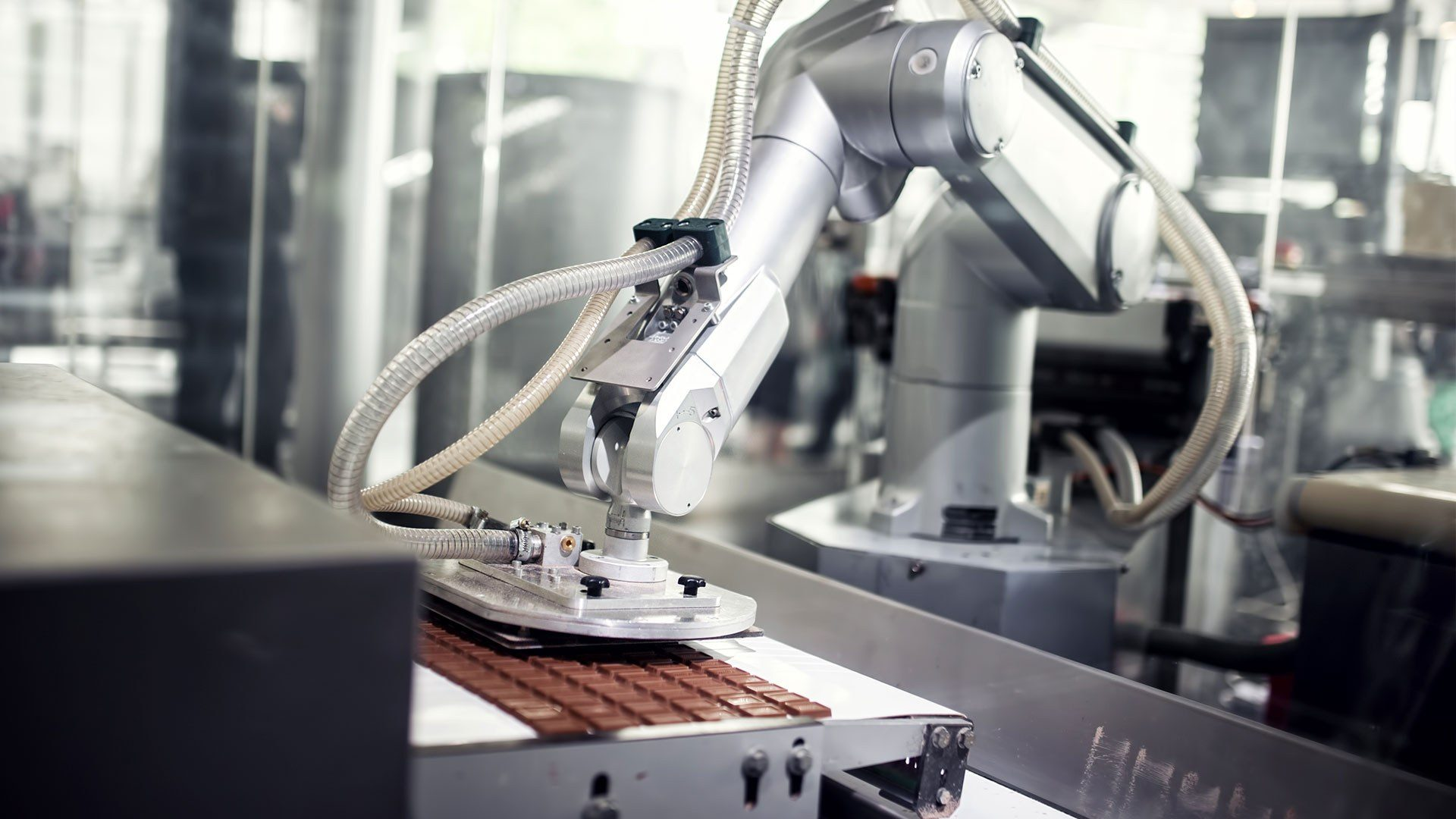 A photo of automated chocolate production with a robot arm
