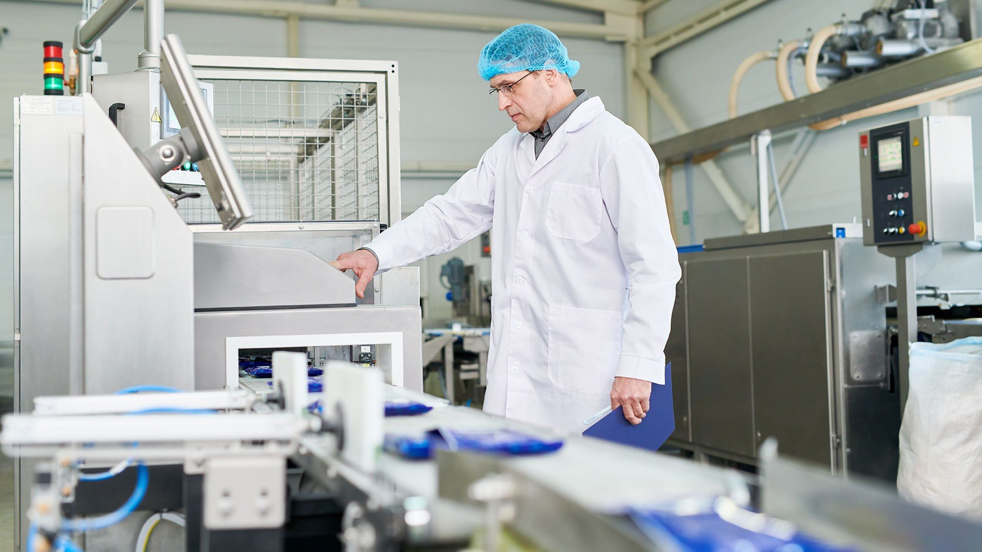 A photo of a food technologist inspecting the production line