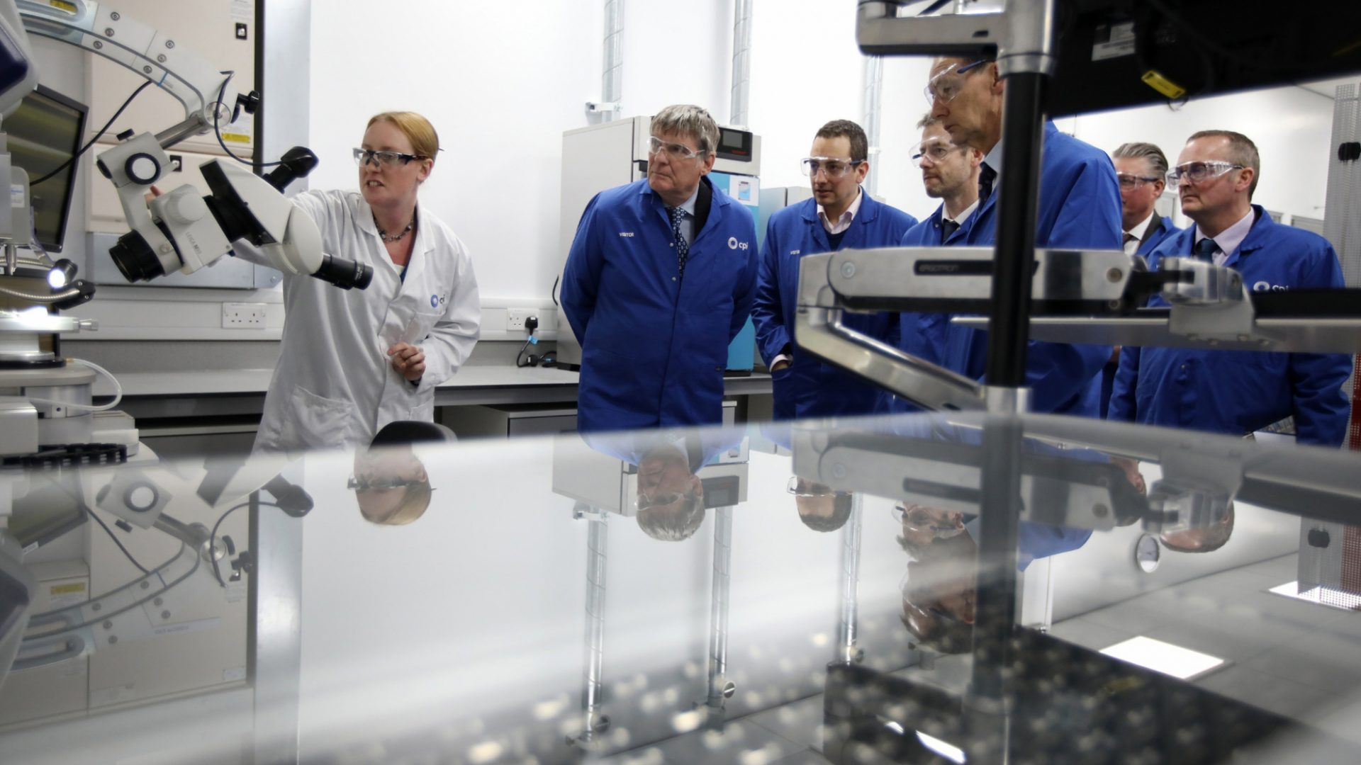 A photo of a CPI scientist giving showing visitors our high-throughput equipment capabilities in a laboratory.