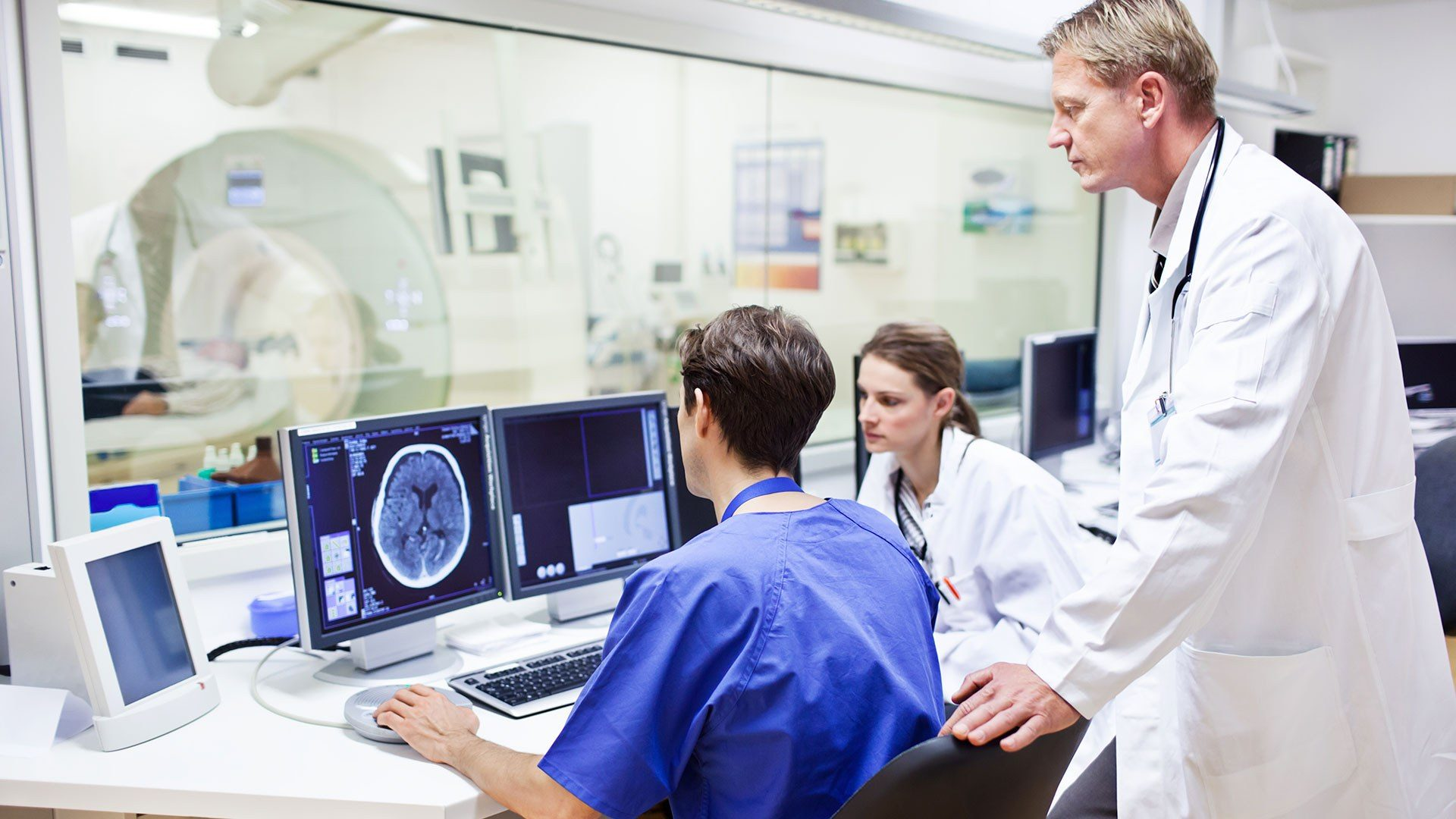 A photo of staff reviewing an MRI scan image