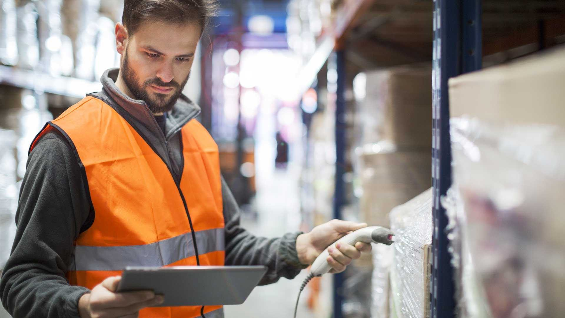 Photo of a man in warehouse scanning parcel