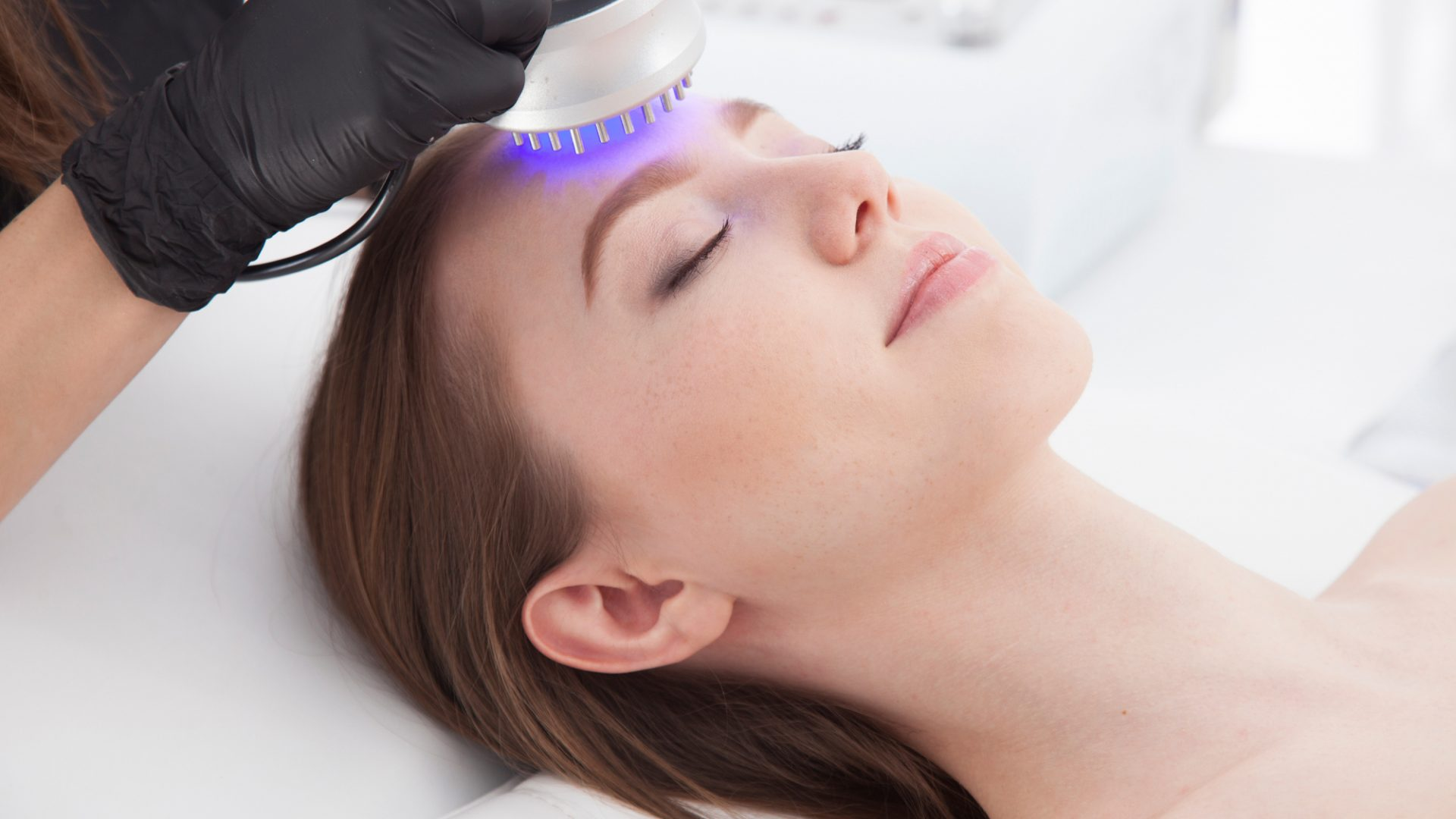 A photo of a woman having skin beauty therapy using photonics